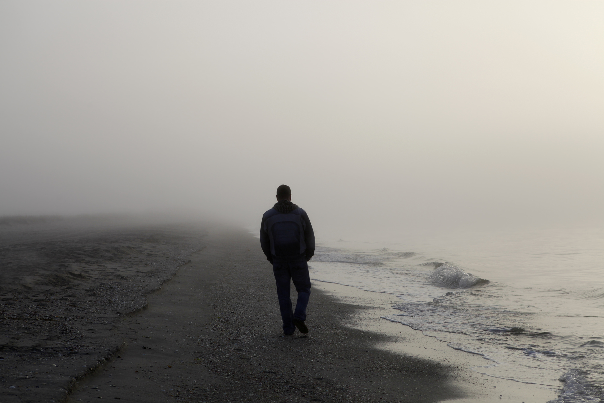 Man walking alone on a foggy beach
