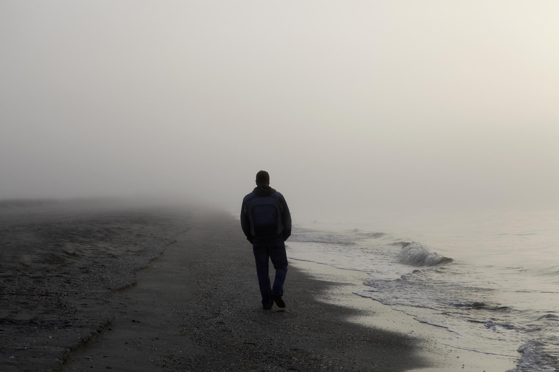 Man walking alone on a foggy beach
